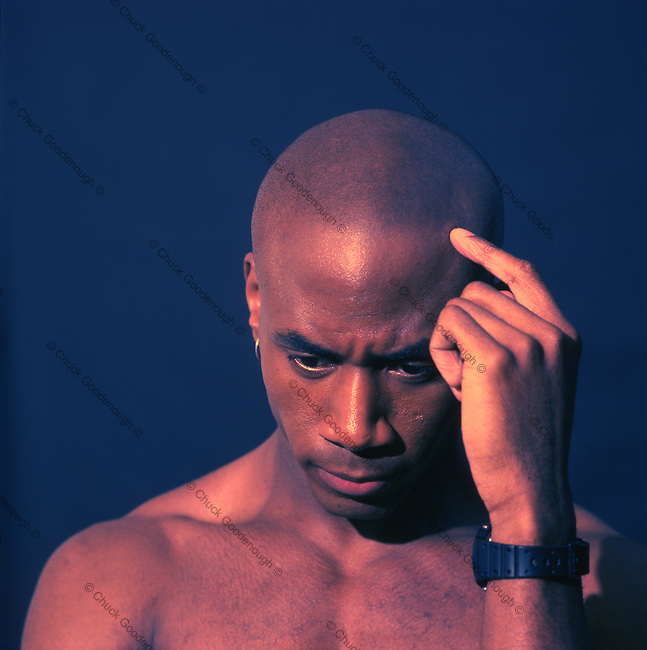 Photo of a Bald African American Man with a finger on his head, Thinking Seriously.