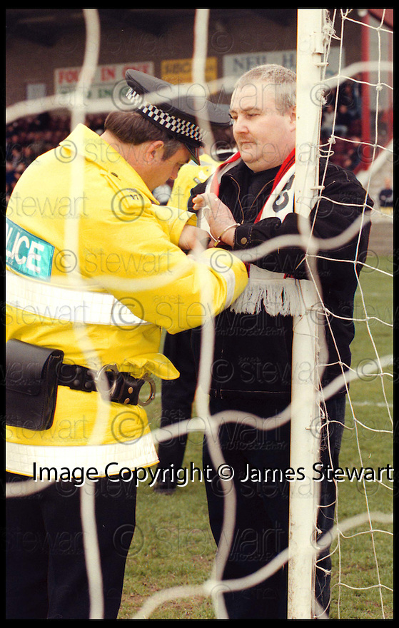 21st March 98      Copyright Pic : James Stewart   .POLICE MOVE IN AS BANKIES FAN DAVIE BROWN PROTESTS AT CLYDEBANKS PROPOSED MOVE TO DUBLIN BY HANDCUFFING HIMSELF TO THE POST DURING THE SECOND HALF...... .Payments to :-.James Stewart Photo Agency, Stewart House, Stewart Road, Falkirk. FK2 7AS      Vat Reg No. 607 6932 25.Office : 01324 630007        Mobile : 0421 416997.If you require further information then contact Jim Stewart on any of the numbers above.........