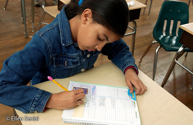 MR / Schenectady, NY / .Yates Arts in Education Magnet School / urban public elementary school / Grade 5.Girl (10, Puerto-Rican American) writes homework assignment in planner.  The school gives fifth graders planning books to help develop organizational skills, ease transition to middle school, and communicate with parents.  Teacher checks each student's planner at end of school day..MR: AD-g5a Ort1..© Ellen B. Senisi