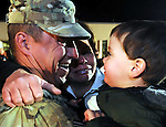 Sgt. Sean Keenan of the Dayville section of Killingly,with a big smile as he looks at his son Gage who he hasn't  seen in 8 months, as his wife Diana cries tears of joy, as 23 members of the 103rd Civil Engineers Squadron returned Monday night,  Feb. 20, 2012,  to the Air national Guard Base in East Granby  from Afghanistan,  they were deployed since last July, the unit had no injuries or deaths during their deployment. (Jim Michaud/Journal Inquirer).