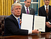 "United States President Donald Trump shows the Executive Order withdrawing the US from the Trans-Pacific Partnership (TPP) after signing it in the Oval Office of the White House in Washington, DC on Monday, January 23, 2017.  The other two Executive Orders concerned a US Government hiring freeze for all departments but the military, and ""Mexico City"" which bans federal funding of abortions overseas.<br /> Credit: Ron Sachs / Pool via CNP"
