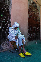 Morocco. Marrakesh medina in the area known as Kasbah. An old man sleeping.