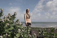 "Indonesia – Sumatra – Band Aceh – Salmi Hardiyanti, a 23-year-old tsunami survivor stands on the beach close to where she grew up. Salmi lost 23 relatives, including her grandparents, two younger sisters and her mother, who was pregnant at that time. Salmi says she will never forget how she felt after seeing the village completely destroyed, the foundations were the only thing left of what was her family house. ""People were telling me they couldn't find my mother. I had never cried so hard and so desperately in my life"". Today, Salmi works as a tourist guide in Banda Aceh, precisely on one of the several tsunami stranded boats which have become a landmark tourist attractions within the city."