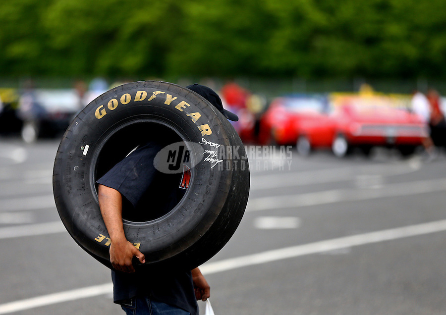 May 30, 2014; Englishtown, NJ, USA; An NHRA fan carries a Goodyear tire through the pits during qualifying for the Summernationals at Raceway Park. Mandatory Credit: Mark J. Rebilas-