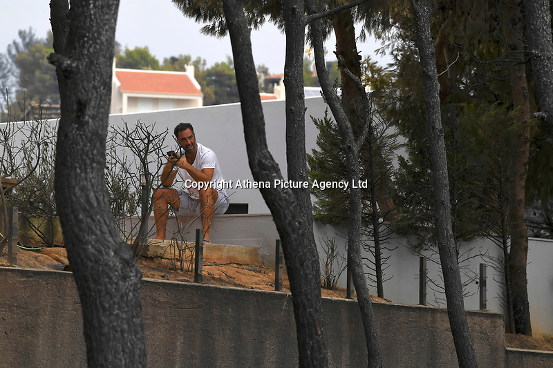 Pictured: A home owner sits in disbelief in the aftermath of the wild forest fires in the Neos Voutzas area near Rafina, Greece. Tuesday 24 July 2018<br /> Re: Deaths caused by wild forest fires throughout Greece.