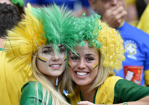 08.07.2014. Estadio Mineirao, Belo Horizonte, Brazil.  Two female supporters of Brazil in face paint and wigs smile on the stand prior to the FIFA World Cup 2014 semi-final soccer match between Brazil and Germany at Estadio Mineirao in Belo Horizonte, Brazil, 08 July 2014.