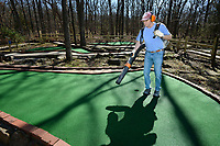 Kenneth Conlee, new co-owner of Gator Golf in Fayetteville, uses a backpack blower Wednesday, March 11, 2020, to clean debris and water from one of two miniature golf courses at the business in Fayetteville. Open since 1987, Gator Golf is open 10 a.m. to 10 p.m. Mondays through Thursdays, 10 a.m. to midnight Fridays and Saturdays, and noon to 10 a.m. on Sundays. Visit nwaonline.com/200312Daily/ for today's photo gallery.<br /> (NWA Democrat-Gazette/Andy Shupe)