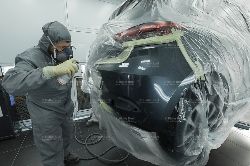 """Switzerland. Canton Geneva. Plan-les-Ouates. Renault Retail Group, RRG Suisse. """"Spot-repair"""" by Dells Angels. Renault Clio car inside a paint booth in auto body repair garage. After filling bumpy part, grinding automobile car body in garage workshop and painting the repaired spot, the mechanic worker is giving the final touch on the repaired spot. 4.03.2020 © 2020 Didier Ruef"""