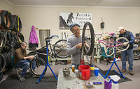 NWA Democrat-Gazette/BEN GOFF @NWABENGOFF<br /> David Tovey (from left) of Rogers, founder of Pedal it Forward NWA, Steve Marquess, a volunteer from Bentonville, and Tim Garton, a voluneer from Bella Vista, tune up and repair bicycles Tuesday, Dec. 26, 2017, at Pedal it Forward NWA in Bentonville.