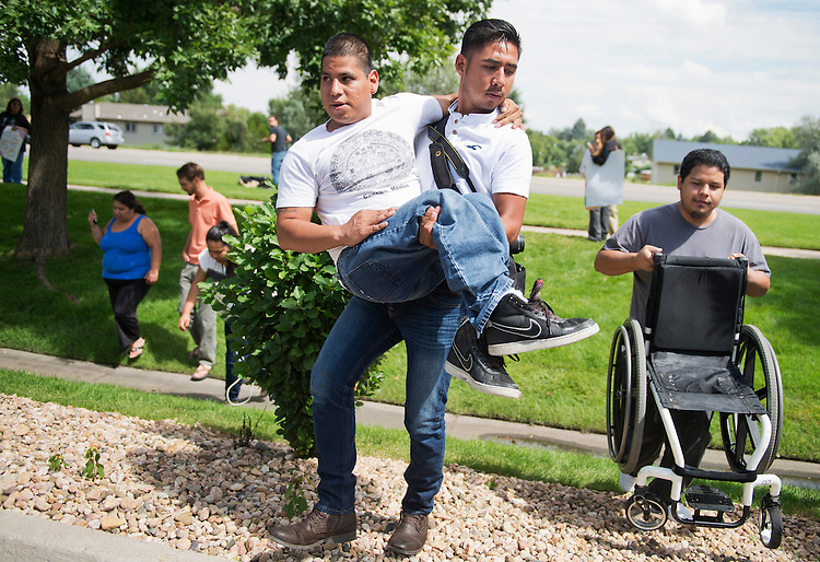 UNITED STATES - AUGUST 27: Hugo Juarez, 26, carries Veni Noya, 22, who suffers from spina bifida, after an action with Dreamers outside the Greeley office of Rep. Cory Gardner, R-Colo., to call for immigration reform, August 27, 2014. (Photo By Tom Williams/CQ Roll Call)