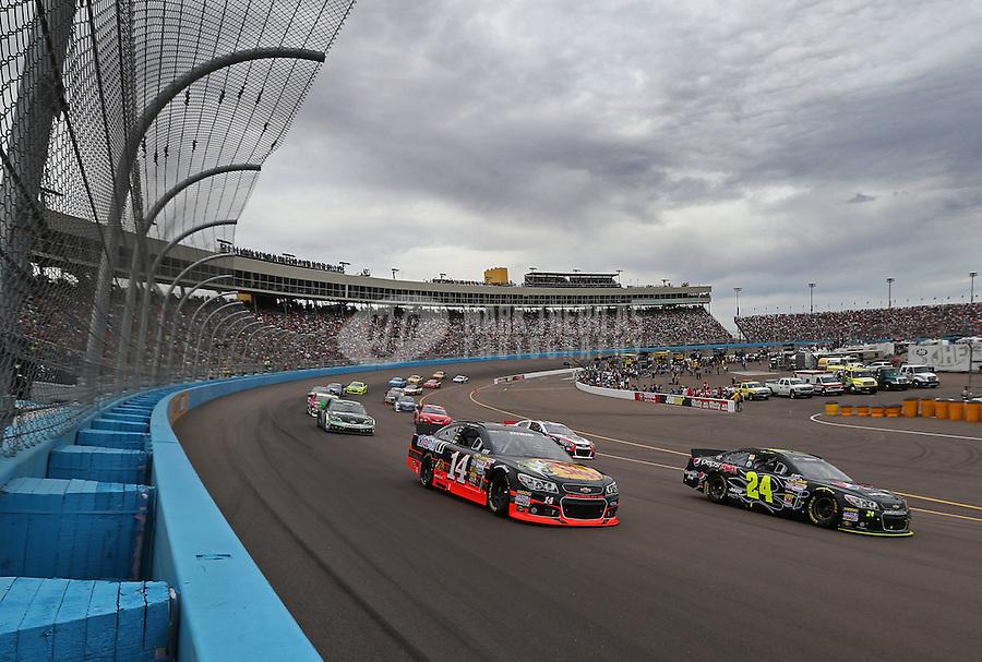 Mar. 3, 2013; Avondale, AZ, USA; NASCAR Sprint Cup Series driver Tony Stewart (14) alongside Jeff Gordon (24) during the Subway Fresh Fit 500 at Phoenix International Raceway. Mandatory Credit: Mark J. Rebilas-