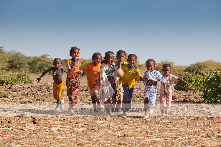 In the seasonal village of Bantagiri in northern Burkina Faso, a group of Fulani children run towards the camera.  The Fulani are traditionally nomadic pastoralists, crisscrossing the Sahel season after season in search of fresh water and green pastures for their cattle and other livestock.