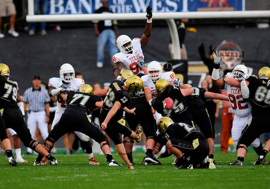 04 October 2008: Colorado placekicker Aric Goodman kicks one of 3 first-half missed field goals against Texas. Rising to try to block the kick is Texas defensive end Brian Orakpo (98). The Texas Longhorns defeated the Colorado Buffaloes 38-14 at Folsom Field in Boulder, Colorado. For Editorial Use Only