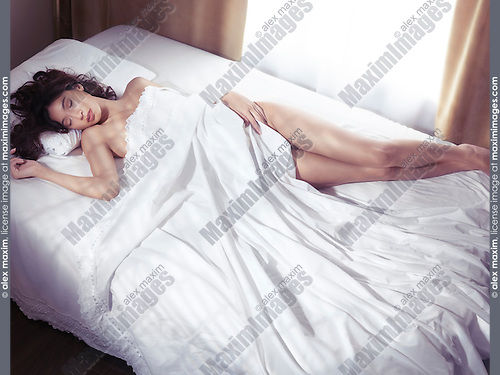 Beautiful young woman sleeping naked in bed covered with white sheets with bright light coming from the window