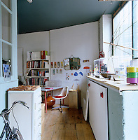 A makeshift home office with an assorted collection of objects and artwork for inspiration