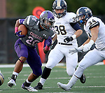 SIOUX FALLS, SD - OCTOBER 4: John Tidwell #26 from the University of Sioux Falls scampers past Dominic Nabak #38 and Bruce Russell #34 from Concordia St. Paul in the first half of their game Saturday evening at Bob Young Field.(Photo by Dave Eggen/Inertia)