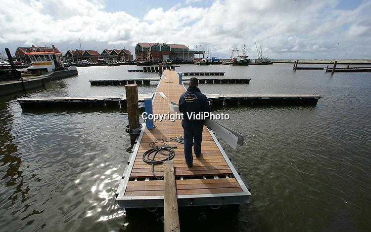 Foto: VidiPhoto..URK - In de haven van Urk wordt op dit moment gewerkt aan een ingrijpende reconstructie, onderdeel van het havenplan dat over een aantal jaren wordt uitgesmeerd. Behalve vernieuwing van de Dormakade en sloop van de oude afslag, komen en er ook zo'n 60 nieuwe ligplaatsen voor met name de recreatievaart. Dat laatste wordt uitgevoerd door de Beens Groep uit Genemuiden. Eind april moet dit onderdeel van het havenplan -dat 3 ton kost- gereed zijn.