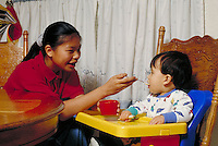 CHINESE-AMERICAN BABYSITTER FEEDING CHILD IN HIGHCHAIR AT KITCHEN TABLE. BABYSITTER AND BABY. OAKLAND CALIFORNIA USA HOME.