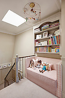 A pink sofa set beneath a wall mounted bookcase on a landing at the top of a staircase provides a spot for children to sit and read.