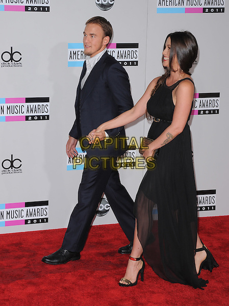 Mario Treadway & Alanis Morissette.2011 American Music Awards - Arrivals held at Nokia Theatre LA Live, Los Angeles, California, USA..November 20th, 2011.ama amas ama's full length black dress sheer sleeveless belt clutch bag gold tattoos blue suit holding hands married husband wife walking side profile .CAP/RKE/DVS.©DVS/RockinExposures/Capital Pictures.
