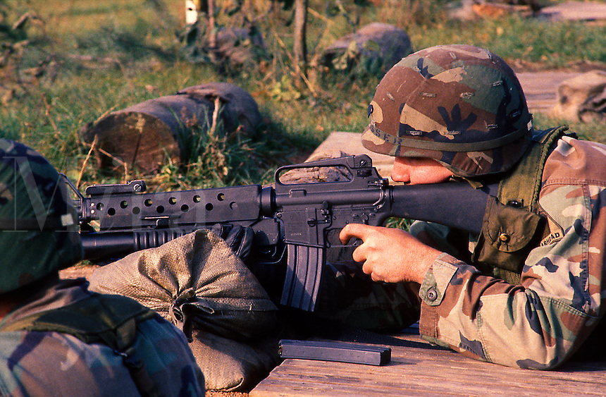 An American soldier in camouflage helmet and uniform takes aim and fires an M-16 rifle during target practice. Germany.