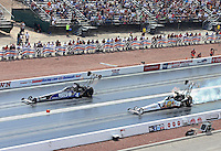 Apr. 7, 2013; Las Vegas, NV, USA: NHRA top fuel dragster driver Antron Brown (left) races down the track alongside a tire smoking Brandon Bernstein during the Summitracing.com Nationals at the Strip at Las Vegas Motor Speedway. Mandatory Credit: Mark J. Rebilas-