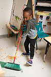 Education preschool 3-4 year olds boy cleaning up spill at meal time using broom to sweep up cereal on floor