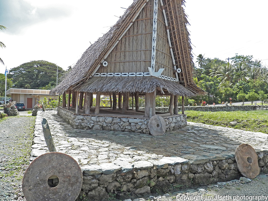 "An historical Yapese ""womens' hut"" with legendary stone money adorning the corners of the stone landing..."