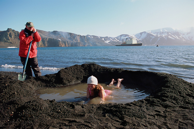 Bather in wooly hat in thermal pool at Whalers Cove. Deception Island. Antarctica