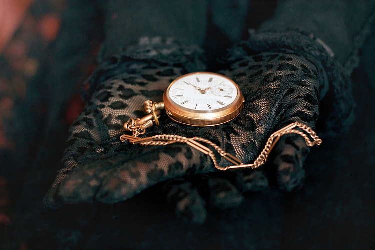 Two hands in black lace gloves holding necklace with open golden pocket watch