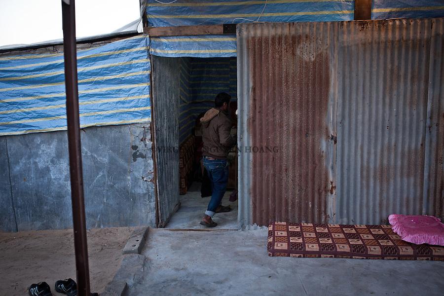 GAZA, Erez Hassan returns home after his day of work . He lives in a small housing made of Zingo ( corrugated iron ) and wood.<br /> <br /> GAZA, Erez: Hassan rentre chez lui apr&egrave;s sa journ&eacute;e de travail. Il vit dans un petit lotissement fait de zingo (t&ocirc;le ondul&eacute;e) et de bois.