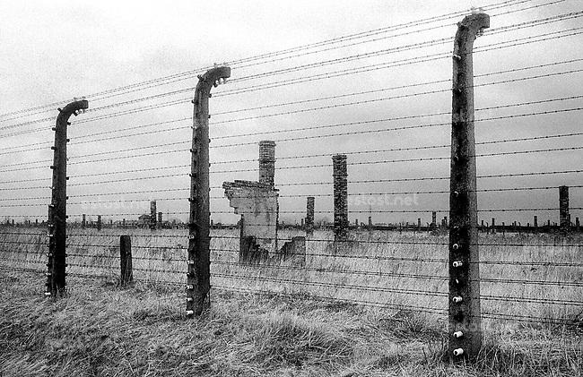 POLEN, 03.1992.Osviecim (Auschwitz).Gedenkstaette K.L. Auschwitz II - Birkenau: Die endlosen Felder mit den Resten der Haeftlingsbaracken (Trennzaeune und Schornsteine)..Former concentration camp: The endless fields mit the remains of the inmates' barracks (chimneys and deviding fences)..© Martin Fejer/est&ost