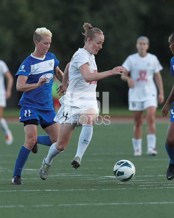 FC Kansas City defender Becky Sauerbrunn (4) on the attack as Boston Breakers midfielder Joanna Lohman (11) closes. In a National Women's Soccer League (NWSL) match, Boston Breakers (blue) defeated FC Kansas City (white), 1-0, at Dilboy Stadium on August 10, 2013.
