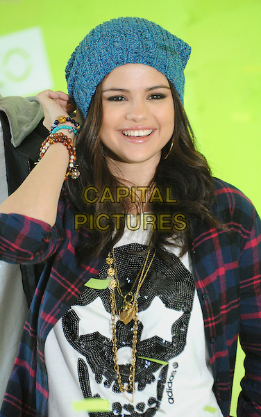 Selena Gomez .Announces new global partnership with iconic fashion brand Adidas Neo Label in Los Angeles, California, USA..November 20th, 2012.half length hand arm blue knitted beanie hat red lumberjack shirt check white shirt black skull print gold necklaces smiling .CAP/ROT/TM.©Tony Michaels/Roth Stock/Capital Pictures