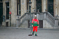An orange-clad street sweeper cleans in Grand Place, Brussels, Belgium