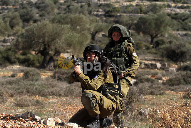 Israeli soldiers stand guard near the site of a fatal shooting incident next to the Palestinian village of Ein Sariya, north of the West Bank city of Ramallah January 29, 2014. Israeli soldiers killed Muhammad Mubarak, 21, on Wednesday who the military said had opened fire on their position near a Jewish settlement in the occupied West Bank. Photo by Issam Rimawi