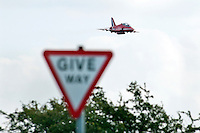 Red Arrows Folland Gnat trainer aeroplane flys over a Give Way road sign during a display at Chatsworth in the Peak District