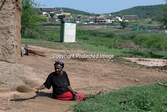 NKANDLA, SOUTH AFRICA - OCTOBER 10: An elderly woman sweeps outside her one-roomed mud house next to the new home for South Africa president Jacob Zuma's in his birth village on October 10, 2012 in KwaNxamalala, Nkandla. South Africa.  The South African government is spending R240-million (about US$ 27 million) to construct the vast property for his large family. (Photo by Per-Anders Pettersson )