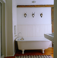 The white bathroom has a ball-and-claw foot bath and three small animal heads displayed on the wall
