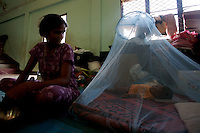 """A woman, displaced by recent bombings in her town, takes care of her baby in the school where she is hosted together with other 400 families in Kinnyia, close to Trincomalee, in Eastern Sri Lanka on Sunday October 08 2006..hundreds of families from the island had to abbandone their homes when caught in the cross fire between LTTE forces and government  forces in early August. .The Sri Lanka civil was is an ongoing conf, The Sri Lanka civil was is an ongoing conflict on the island nation of Sri Lanka Since the 1983 """"Black July""""  pogrom there has been on and off civil war, mostly between the government and the Liberation Tigers of Tamil Eelam, or the LTTE, who want to create an independent state of Tamil Eelam in the north east of the island. It is estimated that the war has left 65000 people dead since 1983 and caused great harm to the population and economy of the country. A cease fire was declared in 2001, but hostilities renewed in late 2005. Following escalation of violence         in July 2006, a senior rebel leader declared the ceasefire null and void, although both sides later reaffirmed their commitment to the ceasefire agreement. Hundreds of people, including military personnel, rebels, and Tamil, Sinhalese and muslim civilians have been killed in fighting this year. Thousands of civilians have been displaced, many coming from areas already stroke by the dec 2004 Tsunami.."""