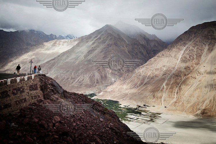Tourists overlook the Nubra Valley and mountains from the Khardung La Pass. The pass is the highest motorable road in the world at 18,380 ft.