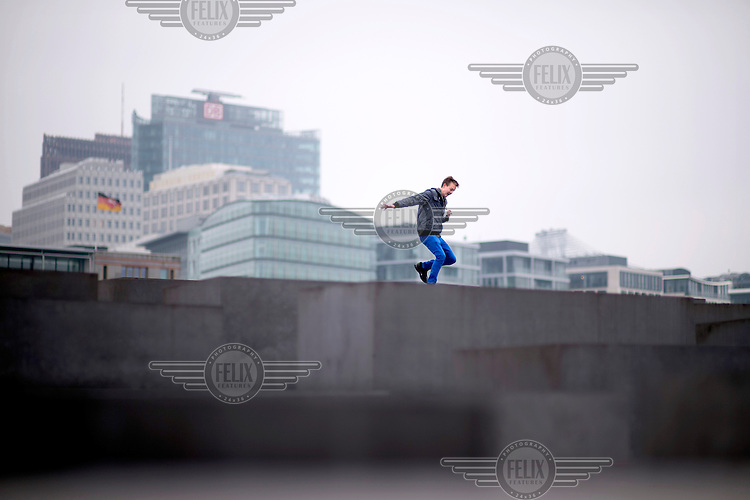 A young man jumping between the stelae that form the Holocaust Memorial. In the background is the Potsdamer Platz.