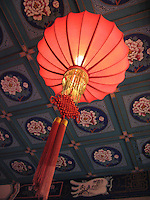 A red Chinese lantern is a dramatic accent against a painted ceiling