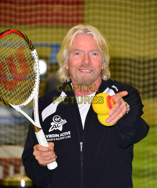 Sir Richard Branson.Press conference & photocall where British tennis star, Laura Robson, becomes Virgin Active's first tennis ambassador & the face of Virgin Active's Junior Tennis Academy, Virgin Active Chiswick Riverside, London, England..February 26th, 2013.half length racquet white black ball goatee facial hair hand finger pointing .CAP/BF.©Bob Fidgeon/Capital Pictures.