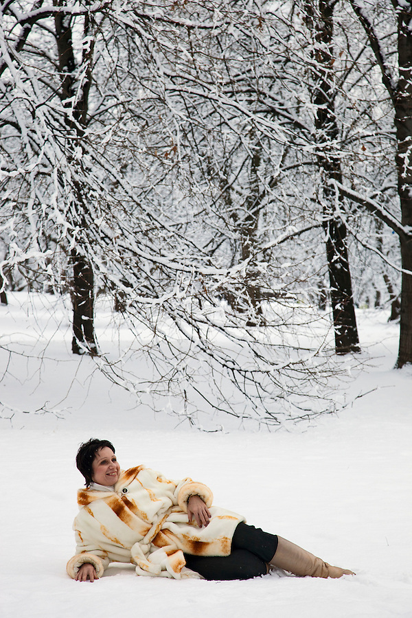 Moscow, Russia, 01/01/2012..A woman sitting in the snow in Kolomenskoe Park on New Year's Day after a heavy overnight snowfall .