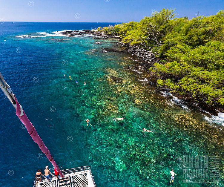 Tourists on a catamaran cruise marvel at the clear waters of the Big Island's Kealakekua Bay; snorkelers dot the reef along the coast.