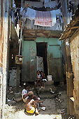 Favela Dona Martha, Rio de Janeiro, Brazil. Skinny children in front of a wooden shack house with washing hanging out from upstairs.
