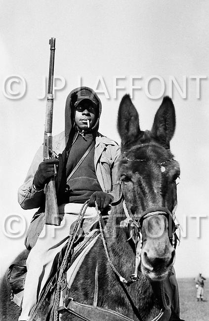 Cummins, AR - February 3rd 1968<br /> A &lsquo;Trusty&rsquo; on horseback holds a rifle while supervising fellow inmates work at the Cummins Unit of the Arkansas State Penitentiary. Life at the prison was unusually harsh and the prison came under fire for crimes against humanity inclosing a prison hospital, which doubled as a torture chamber. <br /> Cummins, Arkansas. 3 f&eacute;vrier 1968.<br /> Cet homme arm&eacute;, sur son cheval, est un prisonnier en fin de peine. On les appelle les &laquo;Trusties &raquo; qui se traduit par &laquo; hommes de confiance &raquo;. Quelques mois avant leur sortie de prison, les lib&eacute;rables deviennent gardiens de leurs coreligionnaires. Ils ont sur eux le pouvoir de vie et de mort.