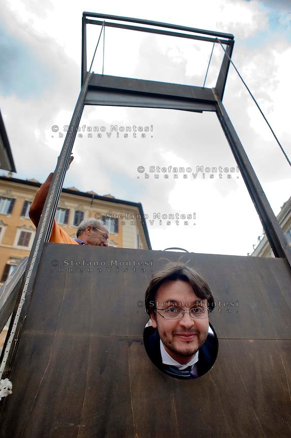 Roma 5 Novembre 2014<br /> Manifestazione davanti al Parlamento, dell'associazione, &quot;Tutti a scuola&quot;, per protestare contro  legge di stabilit&agrave; del Governo Renzi, che taglia i  fondo nazionale della non autosufficienza e   cancella i diritti dei disabili. I manifestanti  portano una ghigliottina per decapitare simbolicamente i politici. Il deputato Matteo Dell'Osso del Movimento Cinque Stelle si sottopone alla ghigliottina.<br /> Rome November 5, 2014 <br /> Demonstration in front of the Parliament of the association &quot;Everybody to School&quot; to protest against the law of stability of the  Prime Minister Renzi's government, which cuts the bottom of national self-sufficiency and cancels out the rights of the disabled. Protesters carry a guillotine to decapitate symbolically politicians. Matteo Dell'Osso deputy Five Star Movement is subjected to the guillotine.