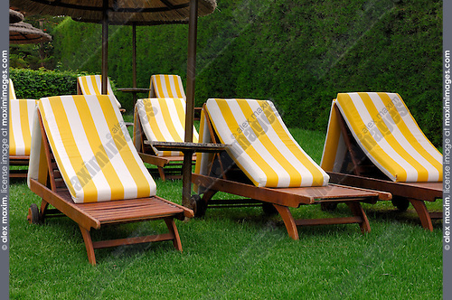Sunbeds on green grass lawn of a hotel